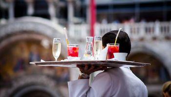 konobar na tacni nosi pića