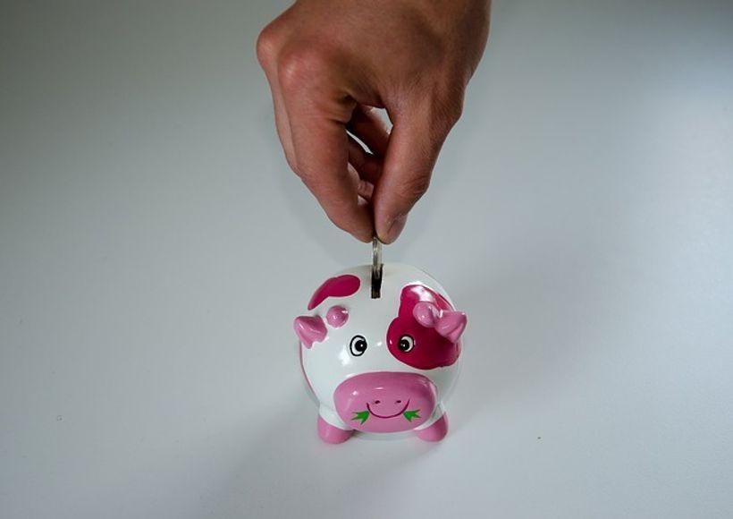 muška ruka ubacuje novčić u kasicu prasicu