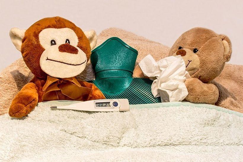 plišani medvjedići leže u krevetu okruženi maramicama i toplomjerom