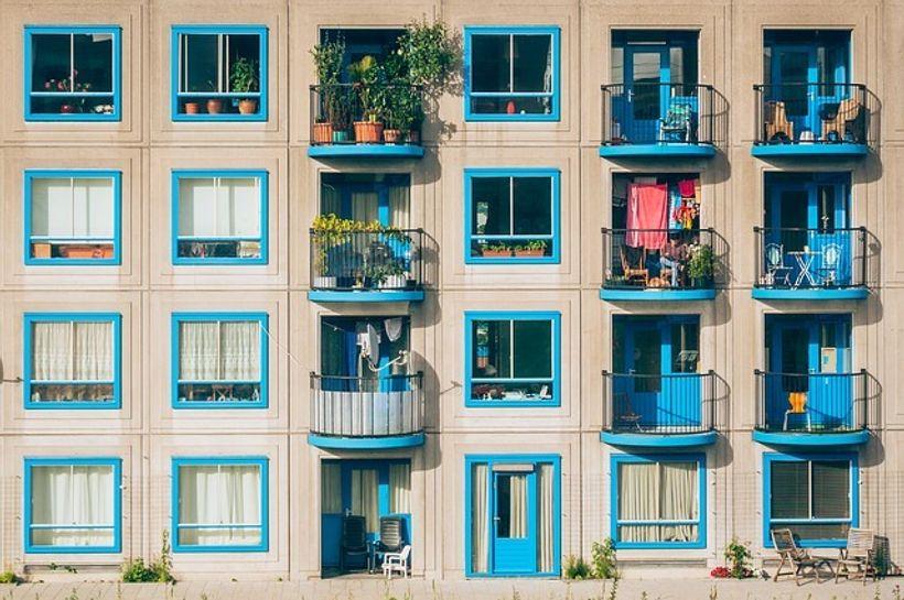 zgrada krem boje s plavim prozorima i balkonima