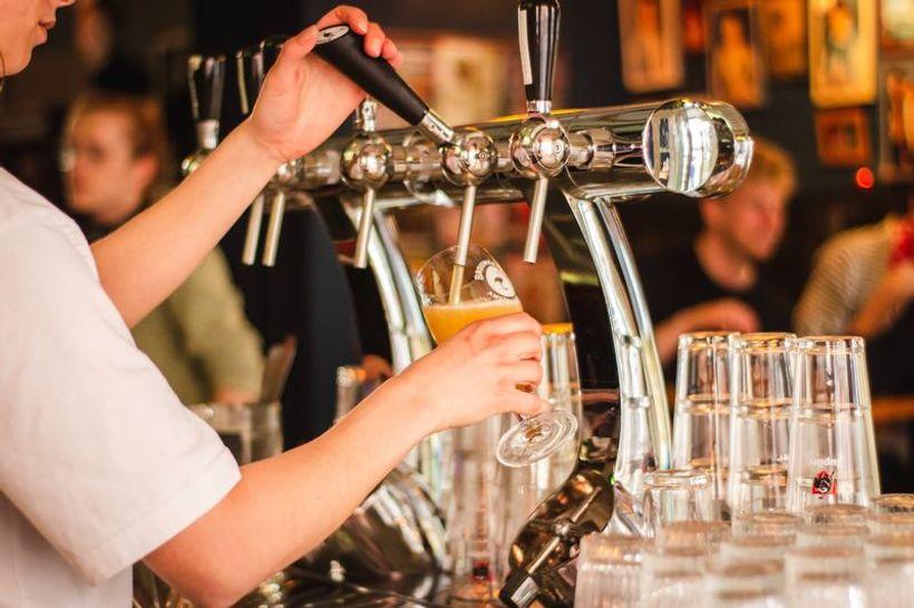 djevojka iz točionika s pivom puni čašu