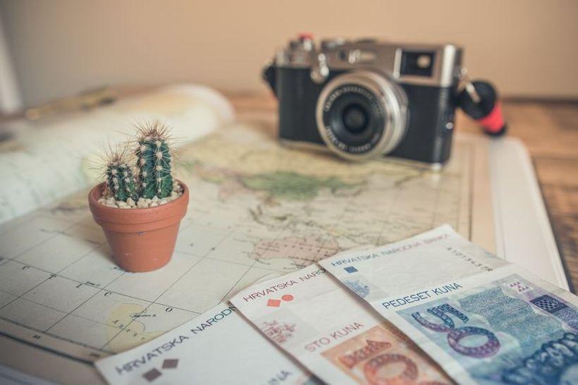 novčanice od 50,100 i 200 kuna, fotoaparat i kaktus na karti svijeta