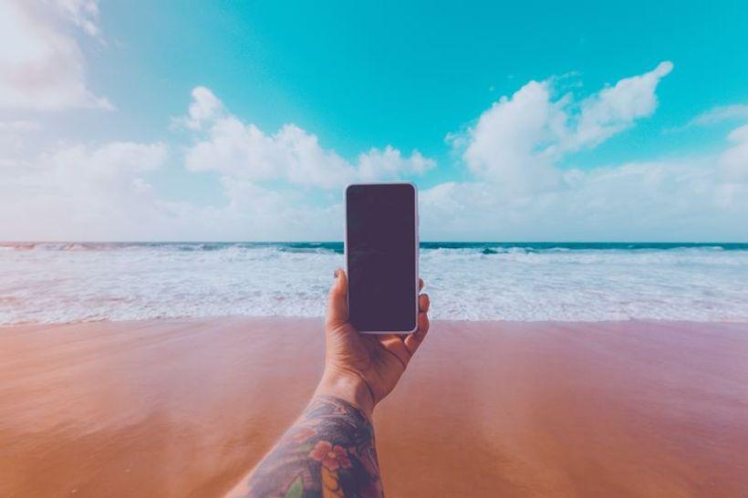ruka drži mobitel na pješčanoj plaži
