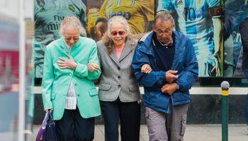 troje umirovljenika, ruku pod ruku, šeće ulicom
