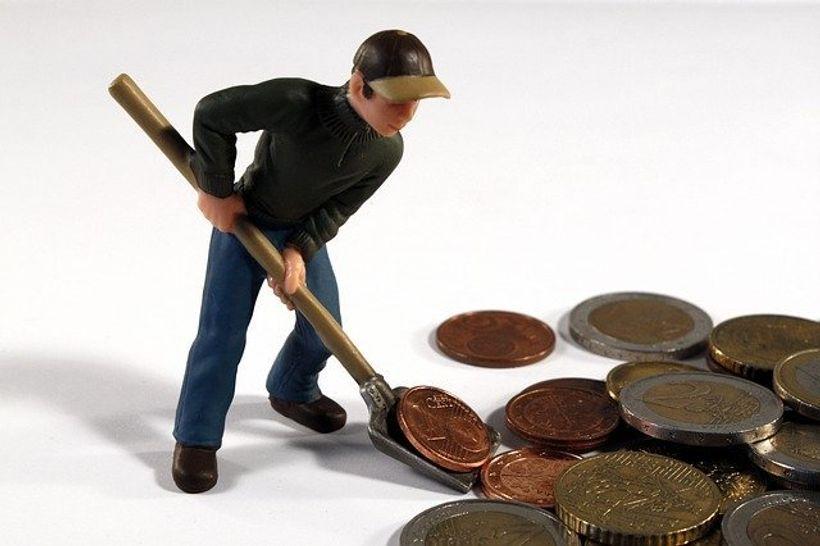 figurica čovjeka s lopatom koji grabi kovanice