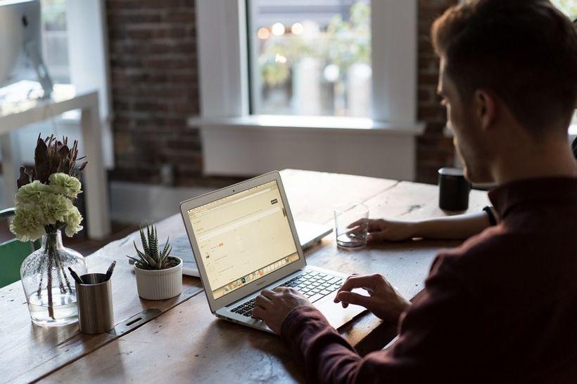 čovjek sjedi za stolom i radi na laptopu