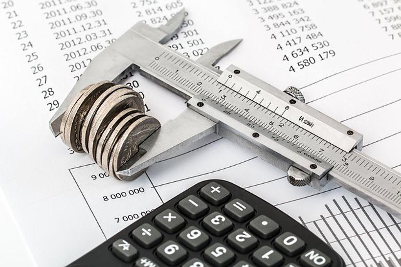 kovanice i kalkulator na hrpi papira