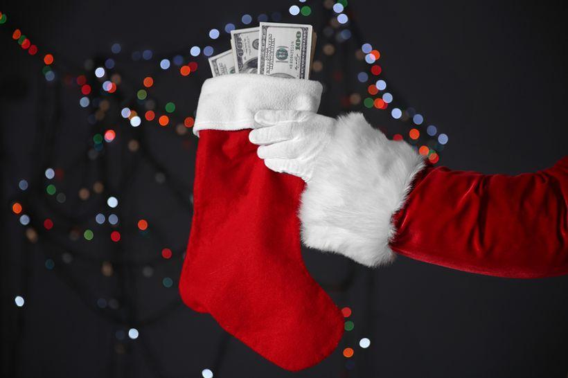 ruka djeda božićnjaka drži božićnu čarapu iz koje viri novac