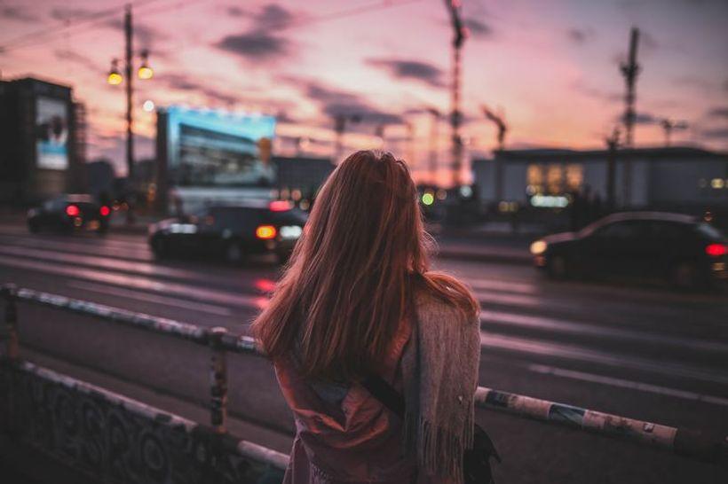 djevojka, okrenuta leđima i naslonjena na ogradu, gleda prolazak automobila na cesti