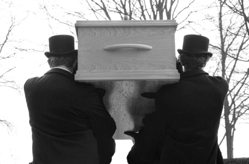 dvojica, u crno odjevena, nosača lijesa