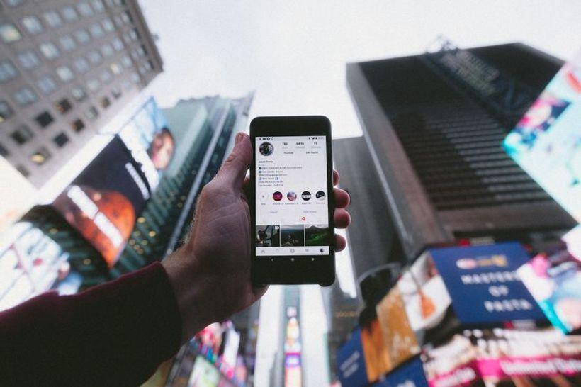 u okruženju nebodera, ruka drži mobitel s otvorenim instagram profilom