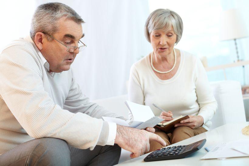 stariji par pregledava račune i koristi se kalkulatorom