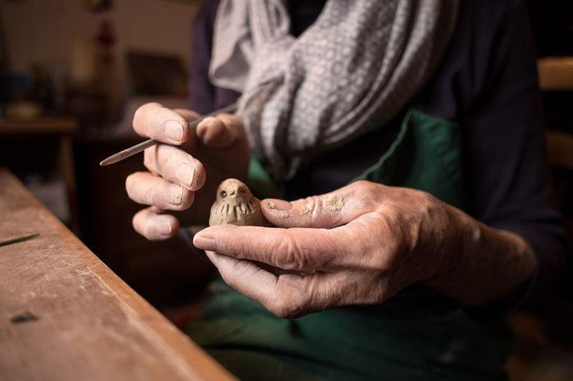 ruke rezbare drvenu ptičicu